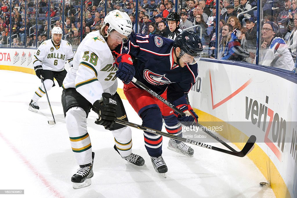 Jordie Benn #58 of the Dallas Stars and Nick Foligno #71 of the Columbus Blue Jackets battle for control of the puck in the corner in the first period on January 28, 2013 at Nationwide Arena in Columbus, Ohio.