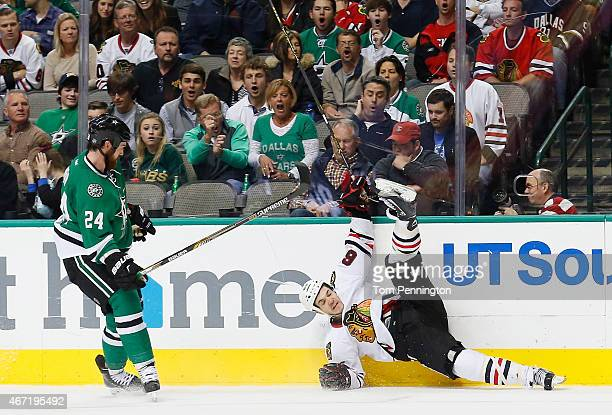 Jordie Benn of the Dallas Stars checks Andrew Shaw of the Chicago Blackhawks into the boards in the second period at American Airlines Center on...
