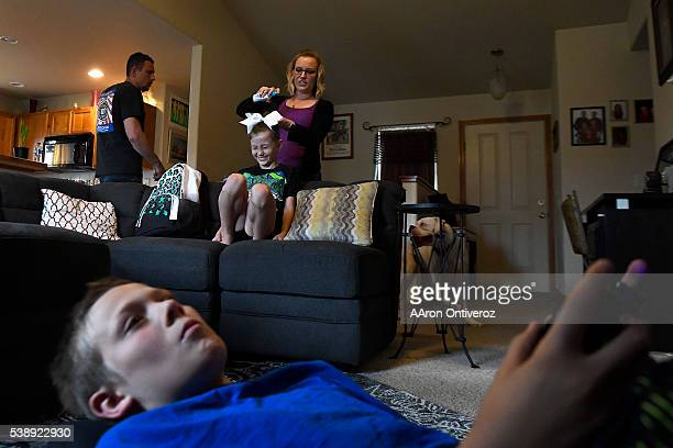 Jordin Terry does her daughter Jeleena's hair before taking her to cheerleading practice in Fort Collins 10 miles away as her son Damionn plays video...