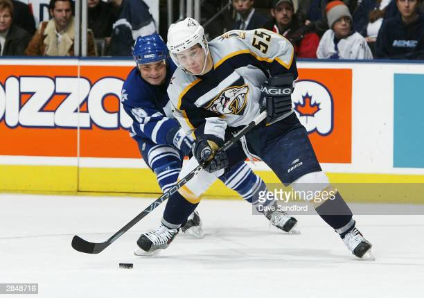 Jordin Tootoo of the Nashville Predators tries to carry the puck away from Tie Domi of the Toronto Maple Leafs during the game at Air Canada Centre...