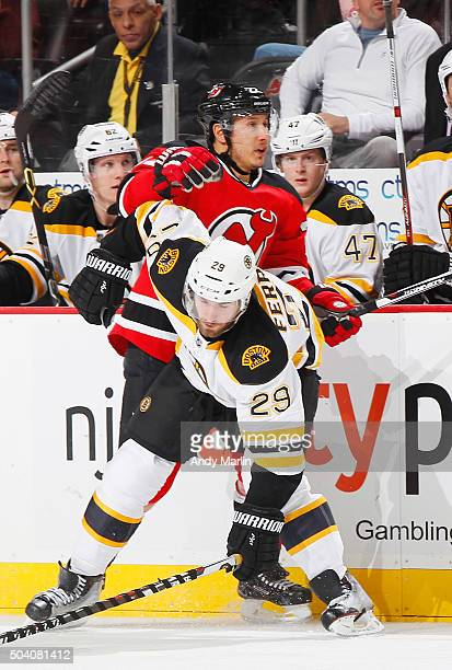 Jordin Tootoo of the New Jersey Devils checks Landon Ferraro of the Boston Bruins during the game at the Prudential Center on January 8 2016 in...