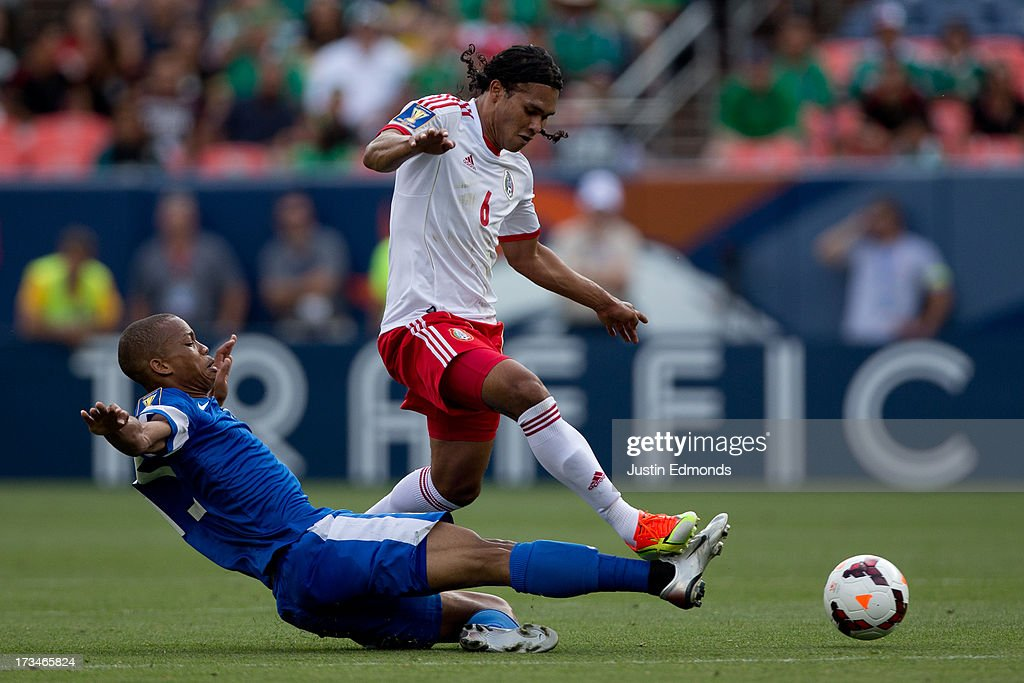 Jordy Delem #15 of Martinique tackles the ball away from Carlos Peña #6 of Mexico during the first half of a CONCACAF Gold Cup match at Sports Authority Field at Mile High on July 14, 2013 in Denver, Colorado.