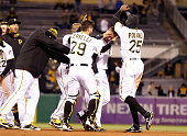 Jordy Mercer of the Pittsburgh Pirates celebrates a walk off RBI single in the eleventh inning with teammates during the game against the St Louis...