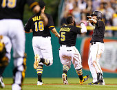 Jordy Mercer of the Pittsburgh Pirates is congratulated by teammates Josh Harrison and Neil Walker after hitting the game winning walk off RBI single...