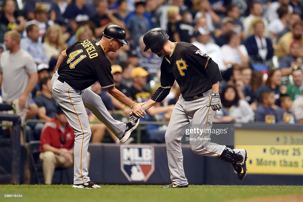 Jordy Mercer of the Pittsburgh Pirates is congratulated by third base coach Rick Sofield following a grand slam homerun during the sixth inning of a...