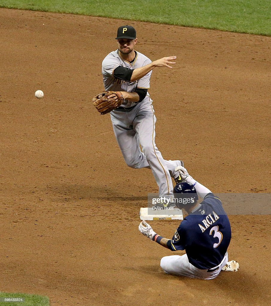 Jordy Mercer of the Pittsburgh Pirates turns a double play past Orlando Arcia of the Milwaukee Brewers in the fifth inning at Miller Park on August...