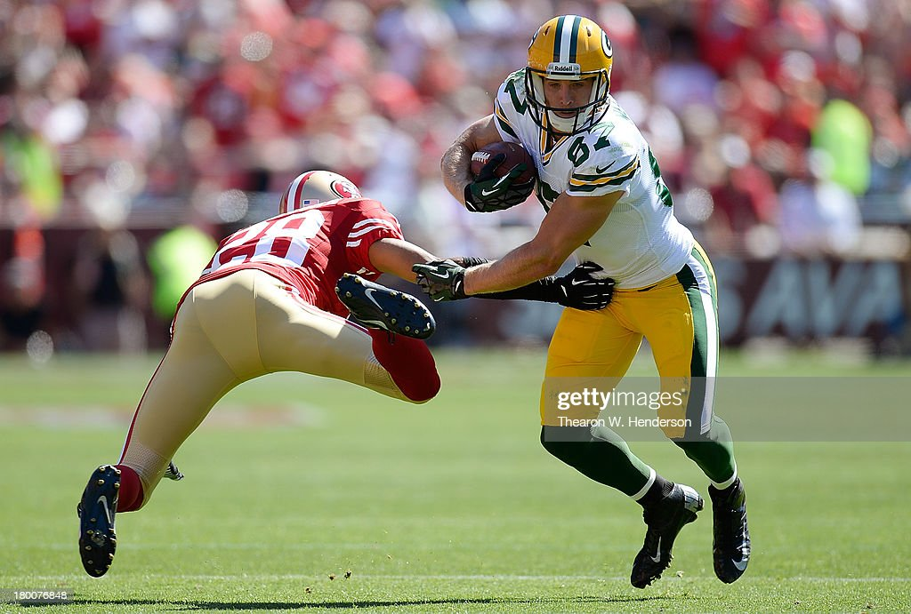 Jordy Nelson of the Green Bay Packers breaks the tackle of Nnamdi Asomugha of the San Francisco 49ers and goes fifteen yards on a pass play during...