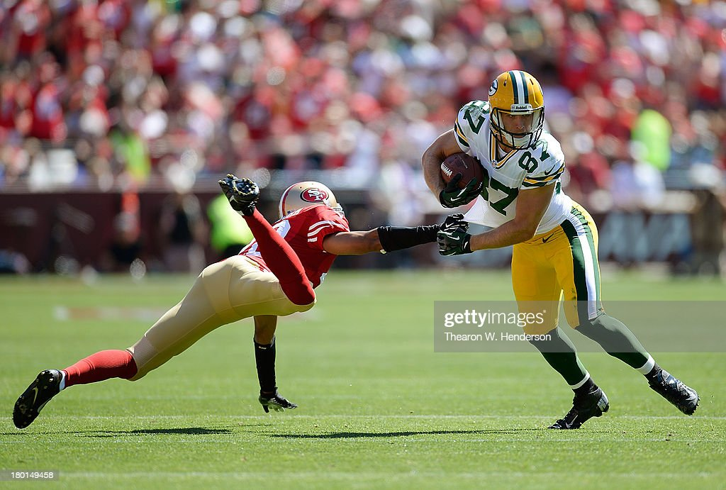 Jordy Nelson #87 of the Green Bay Packers breaks the tackle of Nnamdi Asomugha #28 of the San Francisco 49ers and goes fifteen yards on a pass play during the second quarter at Candlestick Park on September 8, 2013 in San Francisco, California.
