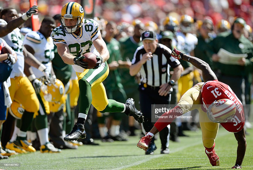 Jordy Nelson #87 of the Green Bay Packers gets knocked out of bounds by Donte Whitner #31 of the San Francisco 49ers after gaining fifteen yards on a pass play during the second quarter at Candlestick Park on September 8, 2013 in San Francisco, California.