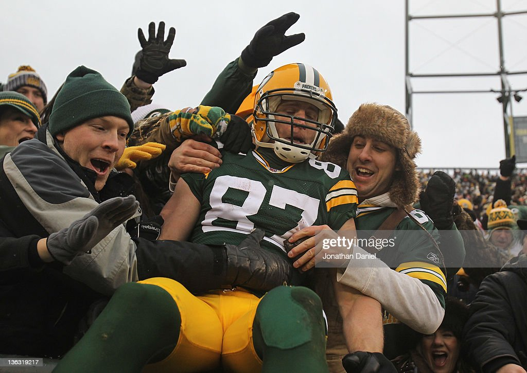 Jordy Nelson of the Green Bay Packers leaps into the stands after scoring a touchdown against the Detroit Lions at Lambeau Field on January 1 2012 in...