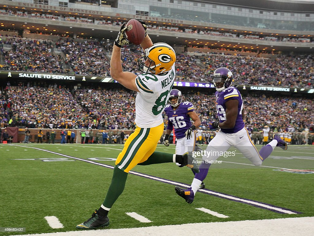 Jordy Nelson of the Green Bay Packers pulls in a pass that was later ruled incomplete while Xavier Rhodes and Robert Blanton of the Minnesota Vikings...