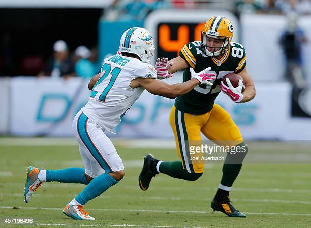 Jordy Nelson of the Green Bay Packers runs with the ball while being defended by Brent Grimes the Miami Dolphins on October 12 2014 at Sun Life...