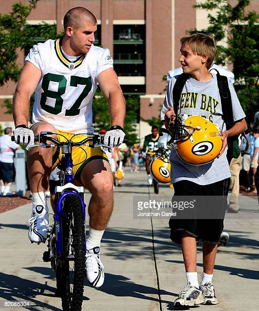 Jordy Nelson of the Green Bay Packers talks to a fan as he rides a bicycle to practice during summer training camp on July 28 2008 at the Hutson...