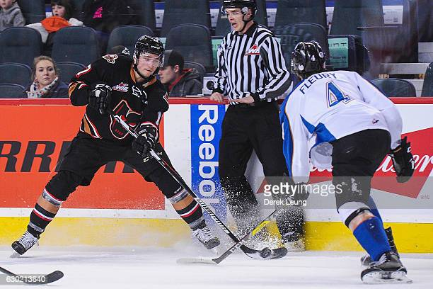 Jordy Stallard of the Calgary Hitmen fights for the puck against Cale Fleury of the Kootenay Ice during a WHL game at Scotiabank Saddledome on...