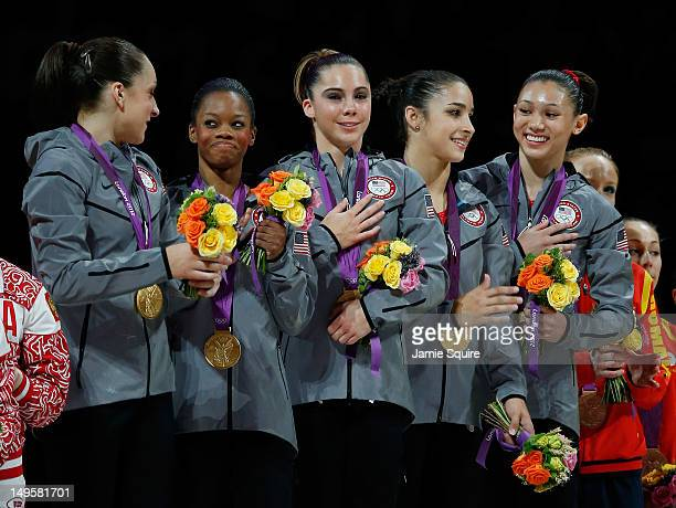 Jordyn Wieber Gabrielle Douglas Mc Kayla Maroney Alexandra Raisman and Kyla Ross of the United States celebrate on the podium after winning the gold...