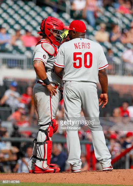 Jorge Alfaro of the Philadelphia Phillies and Hector Neris speak at the mound in the ninth inning of an MLB game against the Atlanta Braves at...