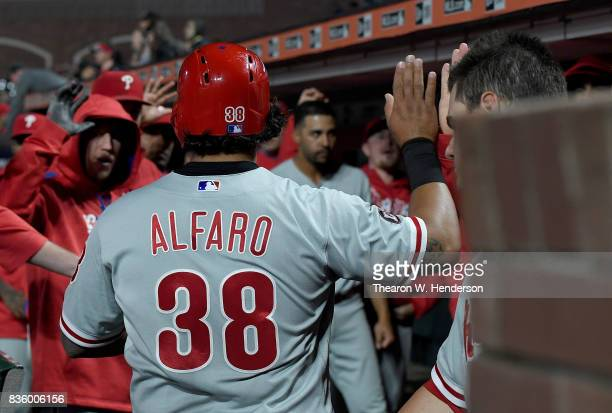 Jorge Alfaro of the Philadelphia Phillies is congratulated by teammates after Alfaro scored against the San Francisco Giants in the top of the eighth...