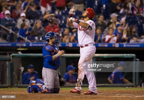 Jorge Alfaro of the Philadelphia Phillies reacts in front of Travis d'Arnaud of the New York Mets after hitting a solo home run in the bottom of the...