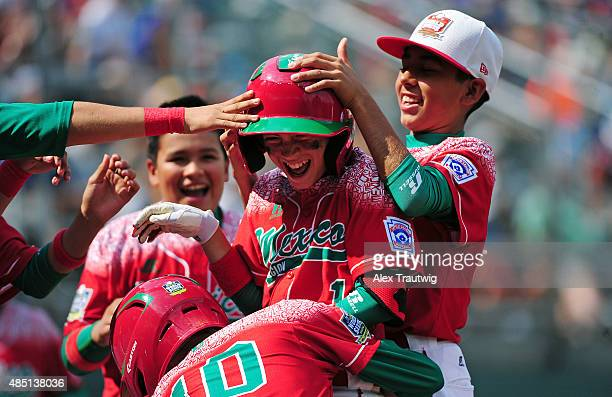 Jorge Armenta of the Mexico team celebrates with teammates after hitting a home run against the Australia team at Volunteer Stadium during Game 17 of...
