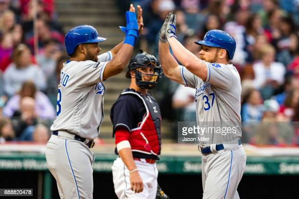 Jorge Bonifacio celebrates with Brandon Moss of the Kansas City Royals as Yan Gomes of the Cleveland Indians watches after Moss hit a three run home...