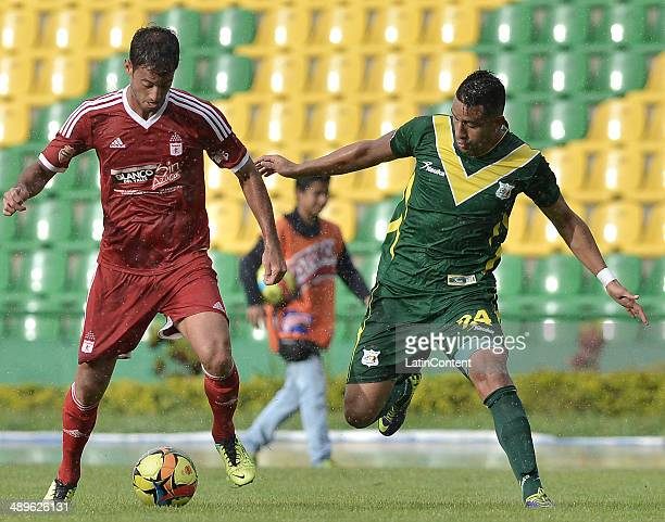 Jorge Brazalez of America de Cali struggles for the ball with Duvan Mejia of Quindio during a match between America de Cali and Deportes Quindio as...