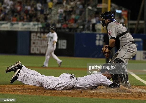 Jorge Cantu of the Florida Marlins scores the winning run off of a hit by Dan Uggla as Rod Barajas of the New York Mets is late with the tag in the...