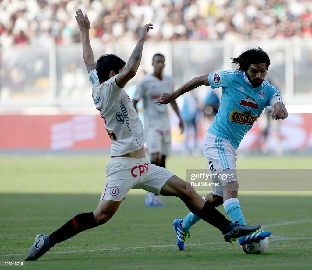 Jorge Cazulo (R) of Sporting Cristal struggles for the ball with Horacio Benincasa (L) of Universitario during a match between Sporting Cristal and Universitario as part of Torneo Apertura 2016 at Nacional Stadium on May 01, 2016 in Lima, Peru.