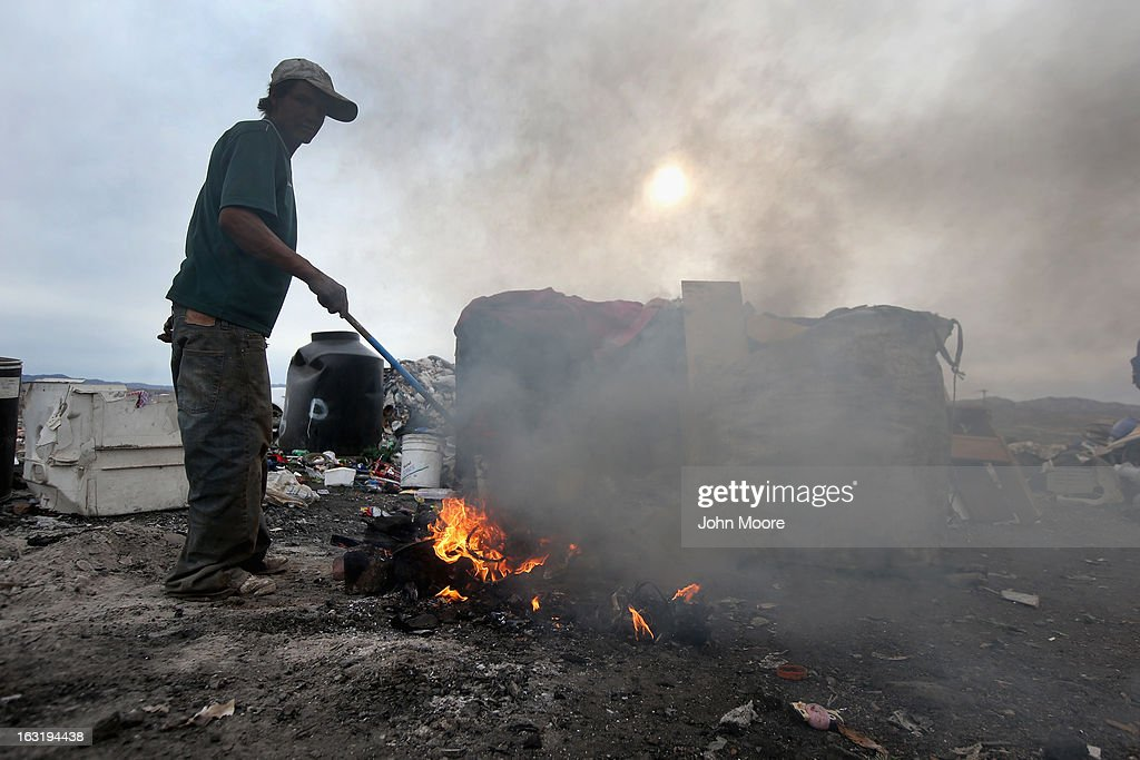 Jorge Dareil burns the plastic off copper wiring he scavenged at the Tirabichi garbage dump on March 5, 2013 in Nogales, Mexico. About 30 families, including Carlos, live at the landfill, searching for recyclables to sell for a living. They have received aid from the non-profit Home of Hope and Peace, which plans to expand it' assistance to the dump's impoverished populace in the future.