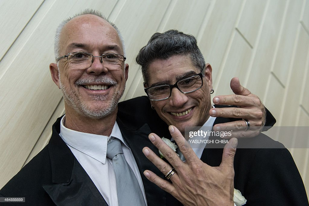Jorge Ferreira (R) and Alex Magalaes pose for a picture after their wedding ceremony at the Court of Justice of the State of Rio de Janeiro in Rio de Janeiro, Brazil, on December 8, 2013. 130 gay couples are getting married in the first massive wedding ceremony since the first gay marriage in Rio de Janeiro in 2011. AFP PHOTO / YASUYOSHI CHIBA