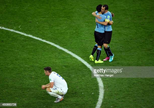 Jorge Fucile and Diego Godin of Uruguay hug as a dejected Gary Cahill of England looks on during the 2014 FIFA World Cup Brazil Group D match between...
