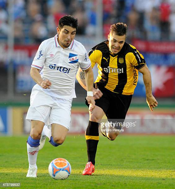 Jorge Fucile of Nacional and Diogo Silvestre of Peñarol fight for the ball during a match between Peñarol and Nacional as part of 12th round of...
