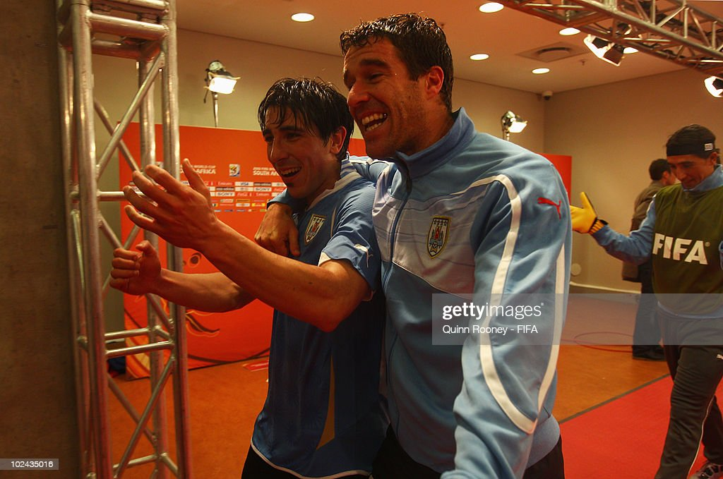 Jorge Fucile of Uruguay celebrates with teammate Andres Scotti after the 2010 FIFA World Cup South Africa Round of Sixteen match between Uruguay and...