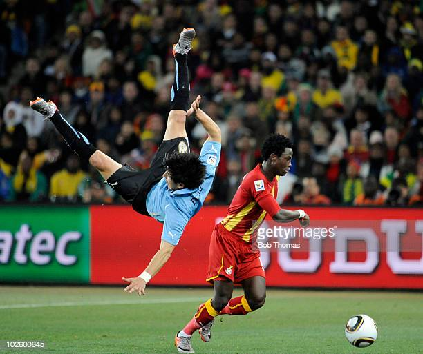 Jorge Fucile of Uruguay in mid air following a high challenge with Samuel Inkoom of Ghana during the 2010 FIFA World Cup South Africa Quarter Final...