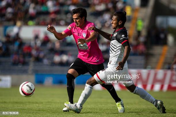 Jorge Hernandez of Pachuca struggles for the ball with Pedro Aquino of Lobos BUAP during the third round match between Lobos BUAP and Pachuca as part...