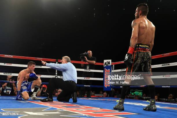 Jorge Linares of Venezuela looks on as Luke Campbell of Great Britain is given an eight count by referee Jack Reiss during the second round of their...