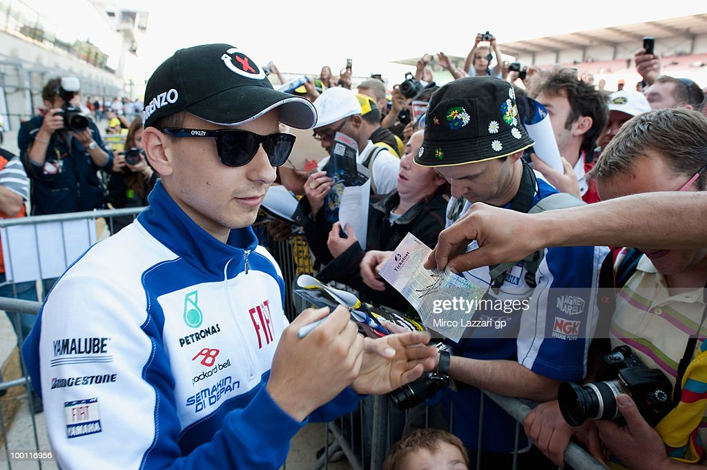 Jorge Lorenzo of Spain and Fiat Yamaha Team signs autographs for fans during the 'Pit Lane Walk' of the MotoGP French Grand Prix in Le Mans Circuit on May 21, 2010 in Le Mans, France.