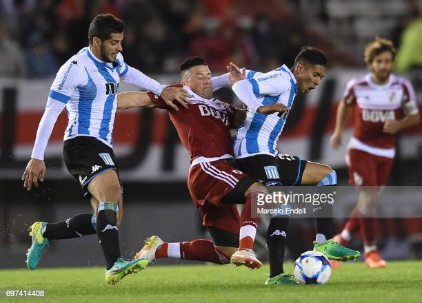 Jorge Luis Moreira of River Plate fights for the ball with Emiliano Insua and Federico Zaracho of Racing Club during a match between River Plate and...