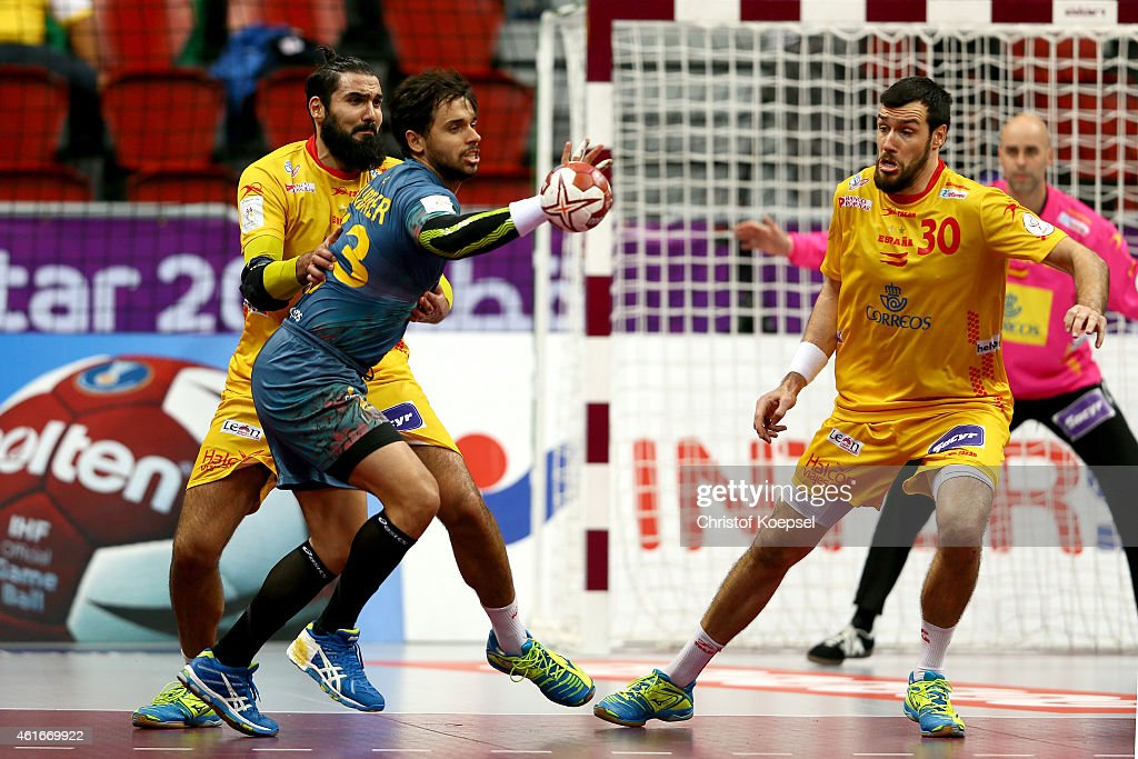 Jorge Maqueda of Spain (L) and Gedeon Guardiola of Spain (R) defend against Diogo Hubner of Brazil (C) during the IHF Men's Handball World Championship group A match between Brazil and Spain at Duhail Handball Sports Hall on January 17, 2015 in Doha, Qatar.