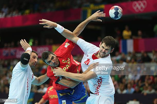Jorge Maqueda Peno of Spain gets under pressure by Igor Vori and Jakov Gojun of Croatia during the Men's Handball preliminaries group B match between...