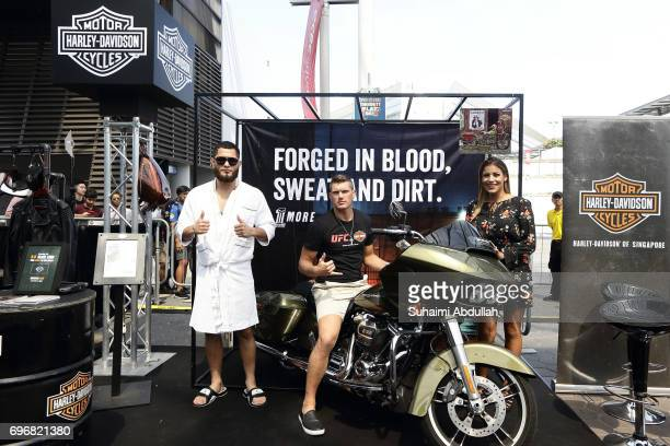 Jorge Masdival Stephen Thomson and Julianna Penna pose for a photo at the Harley Davidson booth during the UFC Fan Experience at OCBC Square on June...