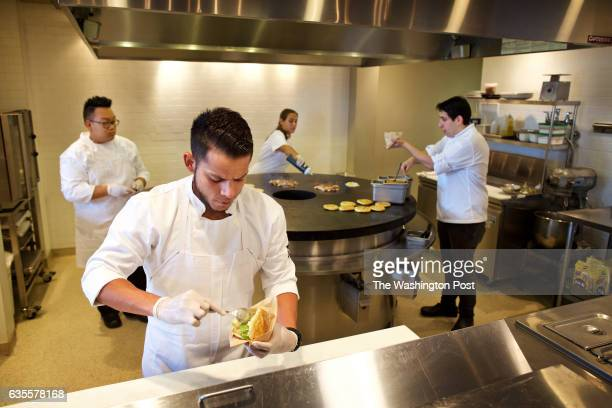 BALTIMORE MD Jorge Ortiz fills an arepa while behind him from left to right Yic Tam Albani Caolo and sous chef Nacho Useche work at the arepas grill...