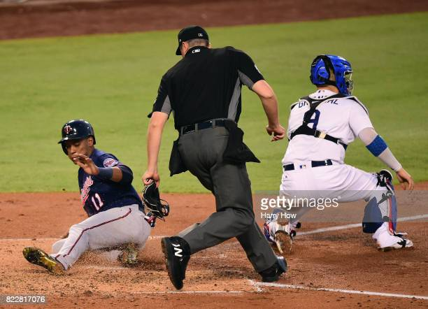 Jorge Polanco of the Minnesota Twins slides past Yasmani Grandal of the Los Angeles Dodgers to score to take a 10 lead during the third inning at...
