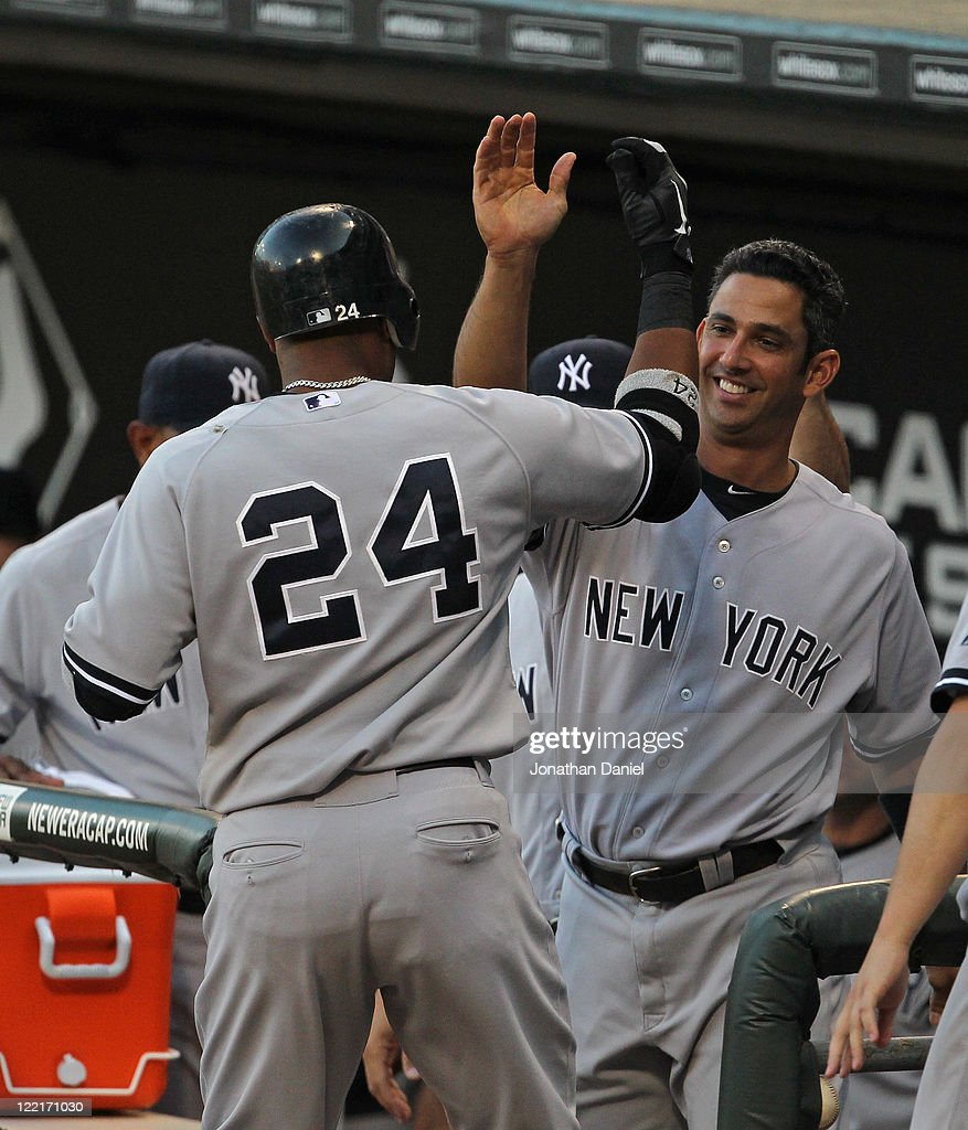 Jorge Posada #20 of the New York Yankees greets teammate Robinson Cano #24 against the Chicago White Sox at U.S. Cellular Field on August 3, 2011 in Chicago, Illinois. The Yankees defeated the White Sox 18-7.