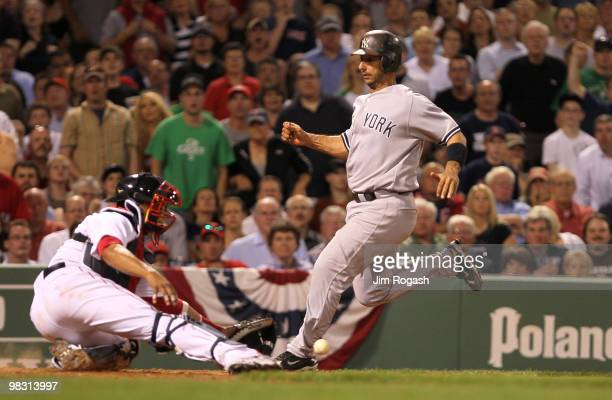 Jorge Posada of the New York Yankees scores as Victor Martinez of the Boston Red Sox fails to handle the throw at Fenway Park on April 7 2010 in...