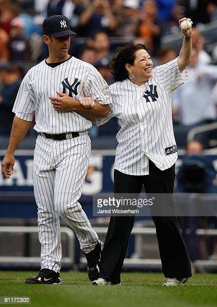 Jorge Posada of the New York Yankees walks Supreme Court Justice Sonia Sotomayor out to the mound during the game on September 26 2009 at Yankee...