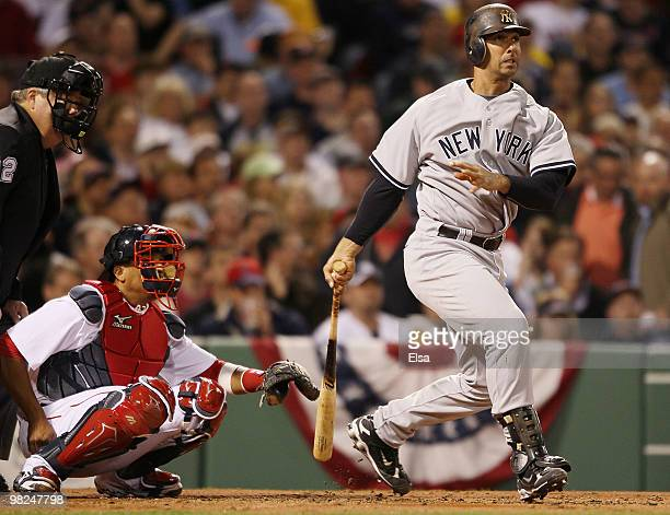 Jorge Posada of the New York Yankees watches his ball hit off the foul pole and into fair territory as Victor Martinez of the Boston Red Sox defends...