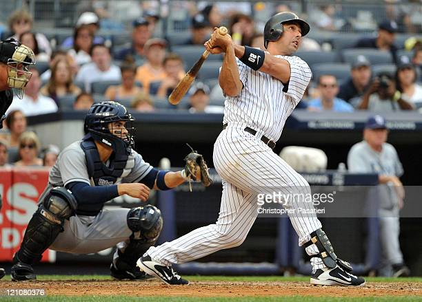 Jorge Posada of the New York Yankees watches his grand slam in the bottom of the fifth inning against the Tampa Bay Rays at Yankee Stadium on August...