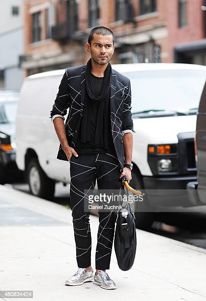 Jorge Rios is seen outside the Tommy Hilfiger show wearing a Tiger of Sweden suit and a Marc Jacobs bag with Made in Mexico shoes during New York...