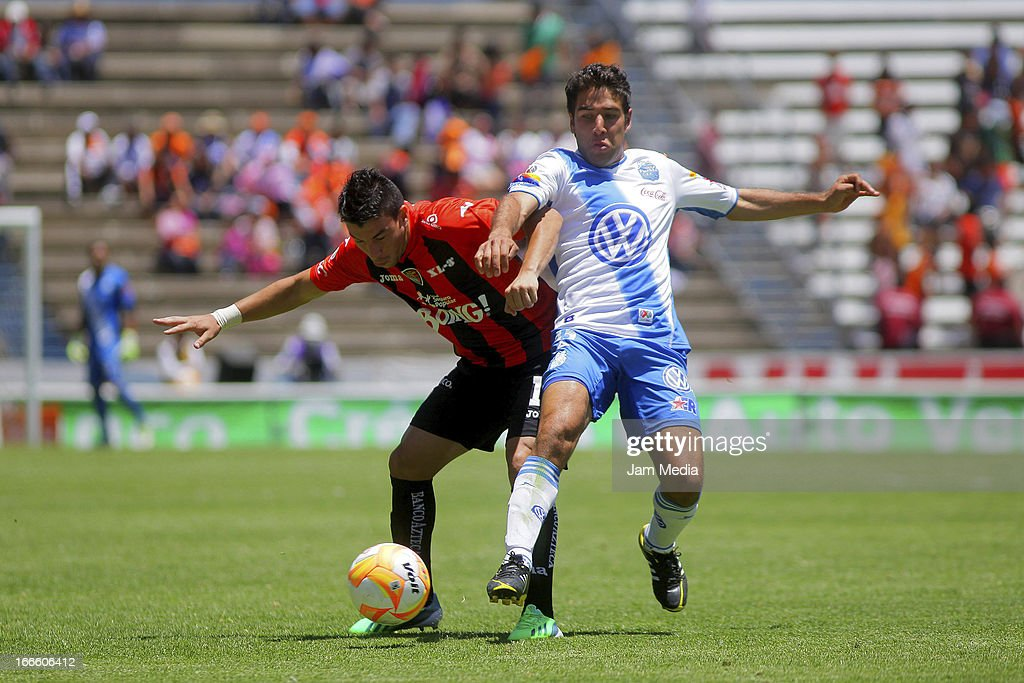 Jorge Rodriguez (L) of Jaguares struggles for the ball with Pablo Gonzalez (R) of Puebla during a match between Jaguares and Puebla as part of Clausura 2013 Liga MX at Cuauhtemoc Stadium on April 14, 2013 in Puebla, Mexico.