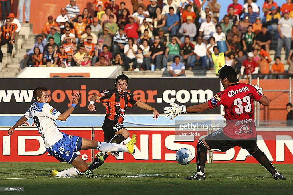 Jorge Rodriguez of Jaguares struggles for the ball with Rodrigo Salinas and Alexandro Alvarez of Puebla during a match as part of the Clausura 2012...